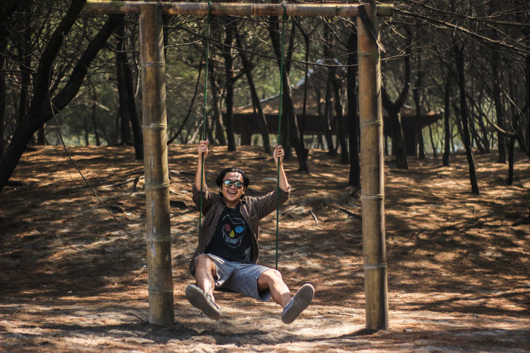 Young man sitting on rope swing in forest
