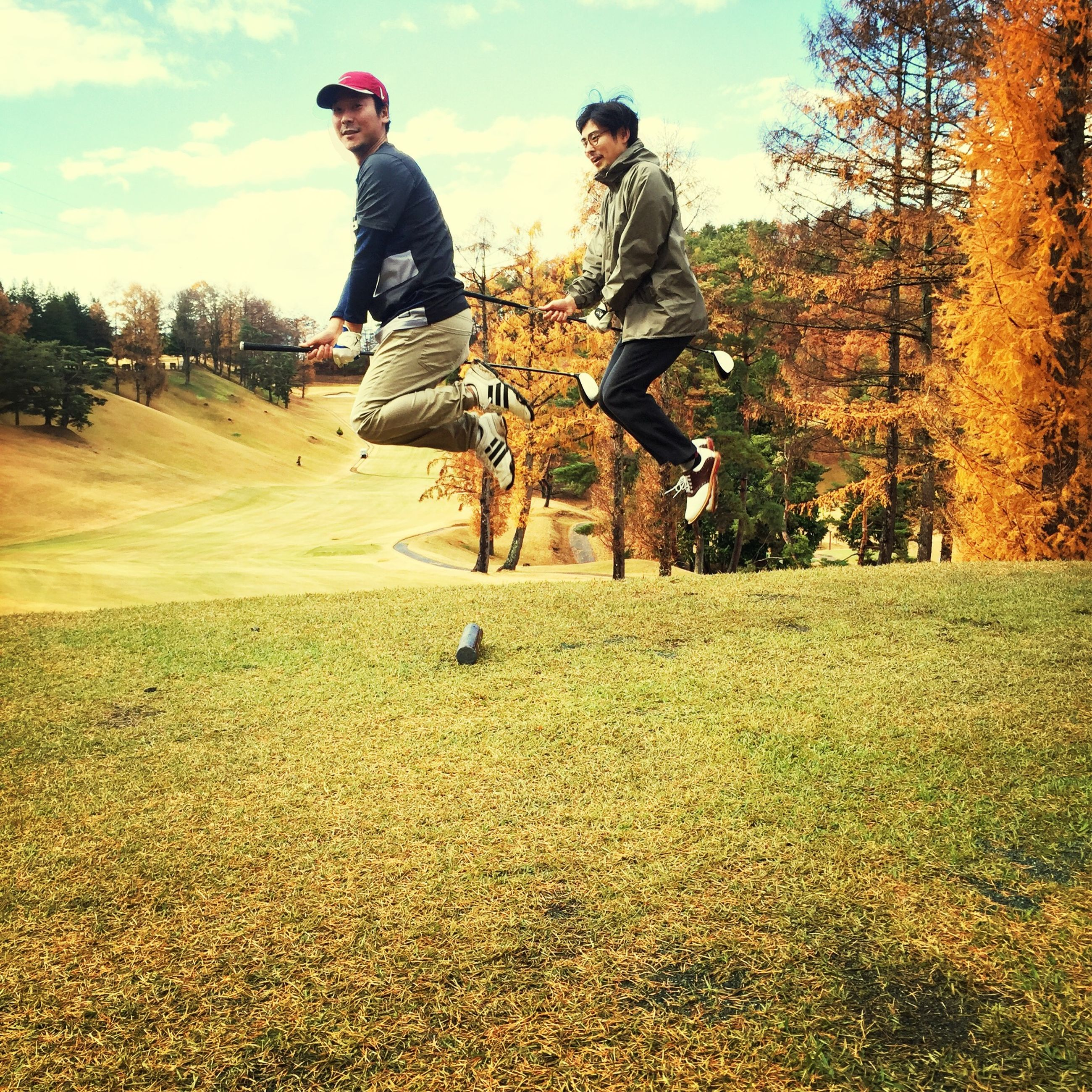 lifestyles, leisure activity, full length, grass, tree, casual clothing, field, person, sky, young adult, jumping, mid-air, standing, enjoyment, young men, fun, men, grassy