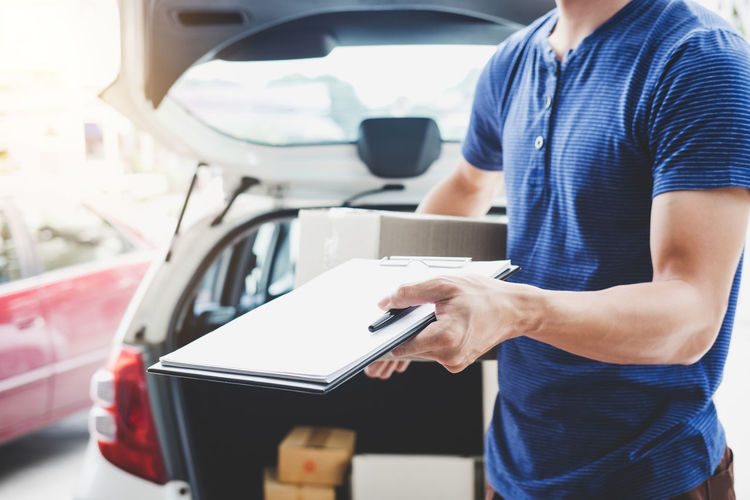 Midsection of man holding clipboard against car