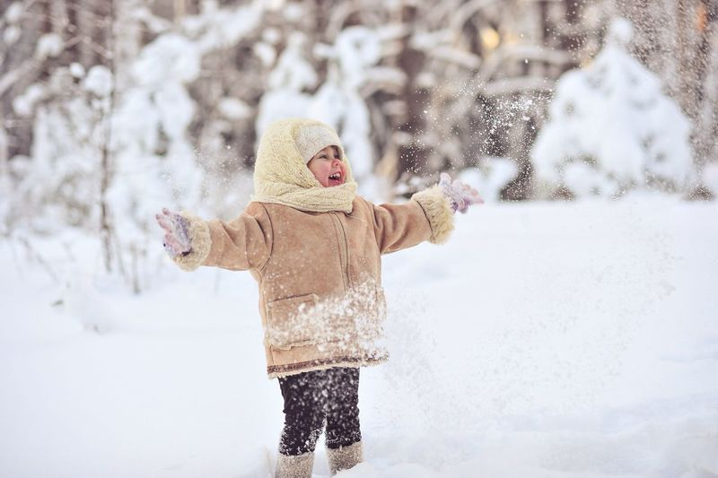 Cute girl playing on snowfield