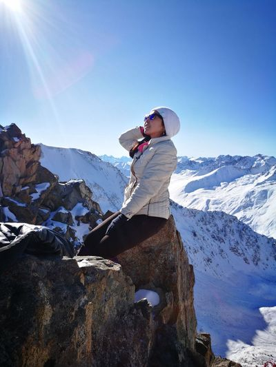 Woman Sitting On Rock At Snowcapped Mountain Against Clear Blue Sky