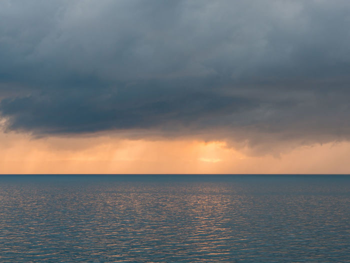 Dark clouds with sunlight over calm sea at sunset with no people Sky Cloud - Sky Sea Horizon Over Water Horizon Water Tranquility Tranquil Scene Scenics - Nature Nature Sunset No People Seascape Idyllic Outdoors Ocean Weather Clouds Cloudy Calm Blue Nobody Croatia Europe Adriatic Sea Mediterranean  Scenics Stormy Weather Light Sunlight Landscape Nature Natural Marine