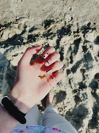 One Person Real People Lifestyles Women Human Body Part Leisure Activity Day Beach Land Sunlight Nature High Angle View Human Hand Hand Body Part Personal Perspective Sand Outdoors Nail Adult
