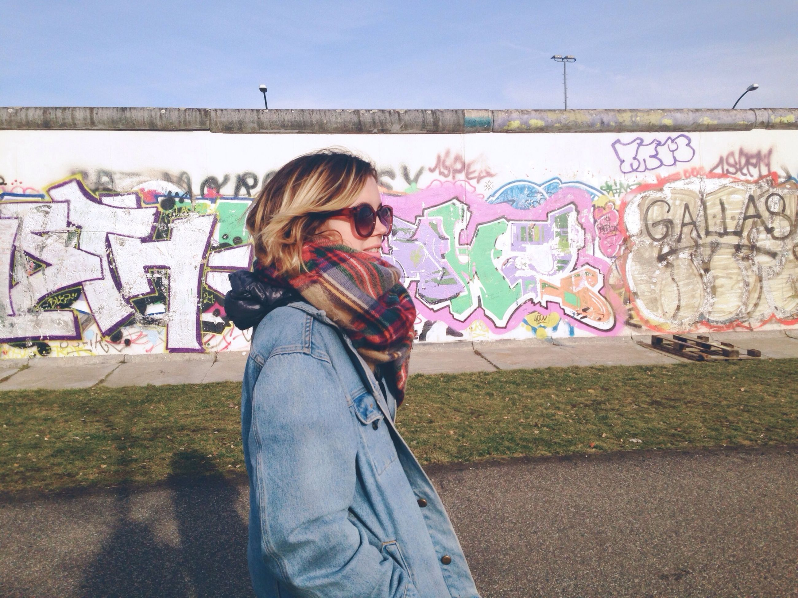 graffiti, person, lifestyles, casual clothing, young adult, leisure activity, standing, looking at camera, young women, portrait, front view, wall - building feature, three quarter length, full length, long hair, smiling, happiness, day