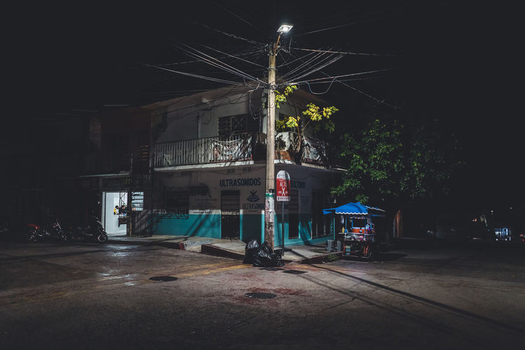 City Architecture Night Building Exterior Built Structure Street Transportation Road Illuminated Building Tree Land Vehicle No People Mode Of Transportation Communication Residential District Nature Motor Vehicle Car Sign Outdoors Dark