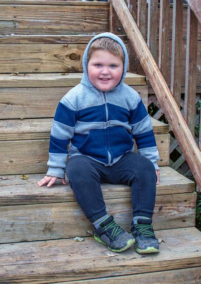 Portrait of boy sitting on wood