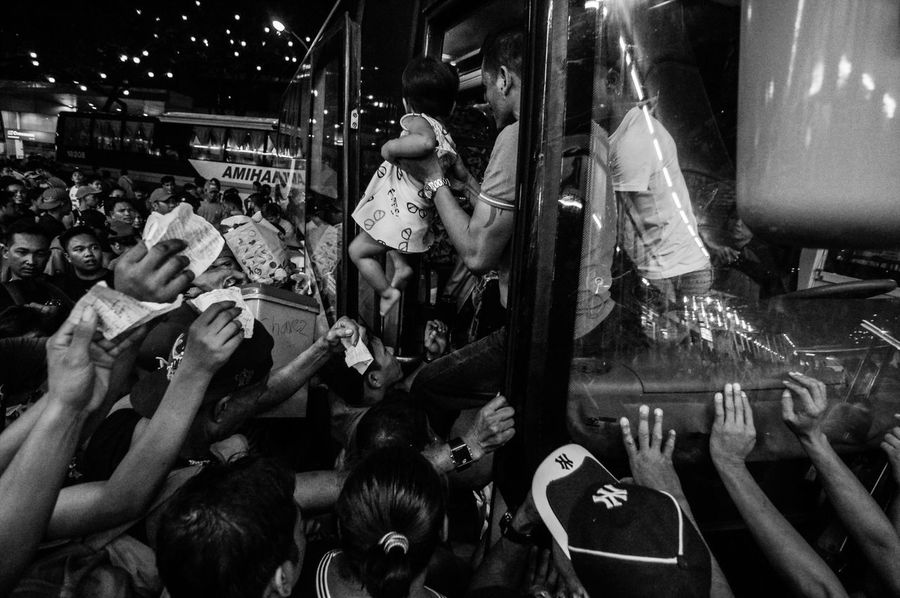 QUEZON CITY, PH - A parent hands over his child to a bus conductor in order to secure a seat as frustrated passengers squeeze their way into each other while raising their tickets up high hoping to be accommodated on a bus travelling to Iloilo in Western Visayas on 27 December 2016. Stranded commuters in Araneta Center Bus Terminal in Cubao ballooned after typhoon Nina (Nock-ten) hit southern parts of Luzon on Christmas, causing enormous delays to provincial busses travelling to and fro Metro Manila three days before New Year's Eve. People Philippines EyeEmBestPics EyeEm Best Shots Eyeem Philippines The Human Condition The Week On Eyem Untold Stories Documentary Photography Larrymonseratepiojo Black And White Everybodystreet MyCommute Traffic Commuters