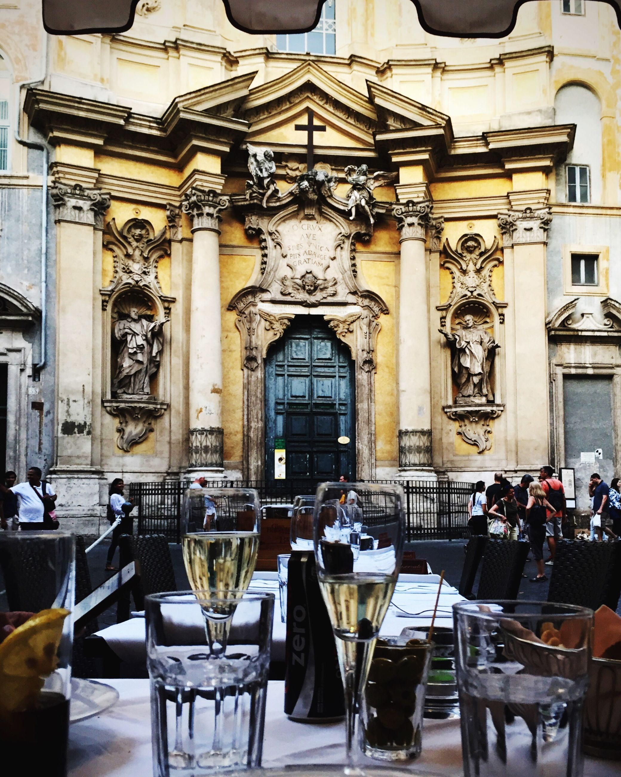 table, chair, restaurant, arrangement, architecture, dining table, place setting, group of objects, facade, history, place of worship, dining, architectural column