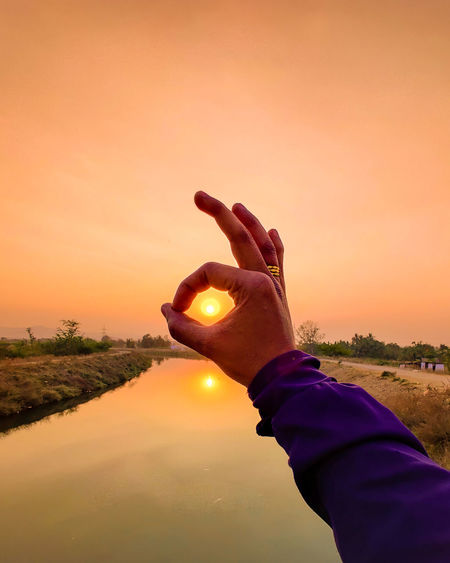 Midsection of man holding sun against orange sky