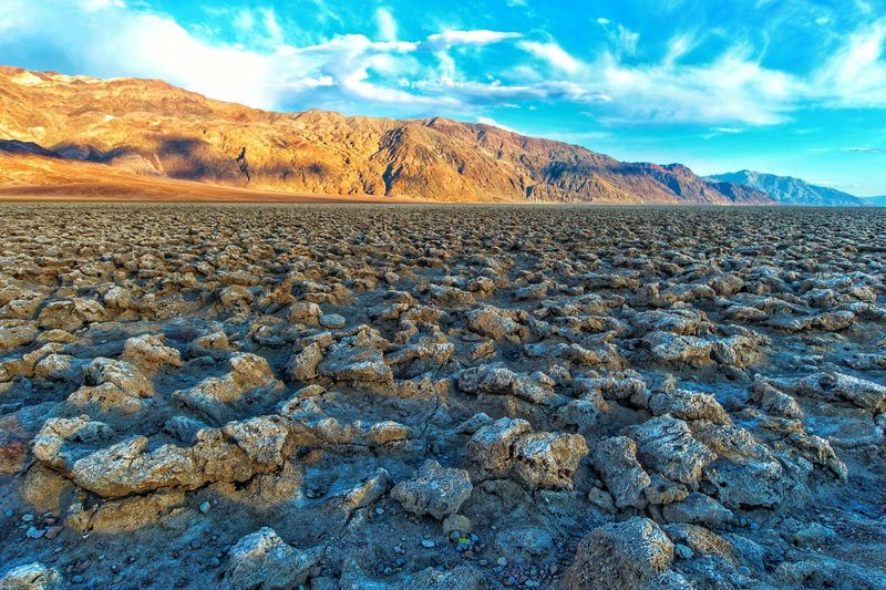 Devils Golf course, Death Valley, California, USA Travel Destinations Devil's Golf Course Devils Golf Course Death Valley, California Death Valley National Park Death Valley Sky Mountain Scenics - Nature Beauty In Nature Tranquil Scene Tranquility Non-urban Scene Cloud - Sky Landscape Nature Environment Land Day Mountain Range No People Solid Remote Rock Idyllic Rock - Object