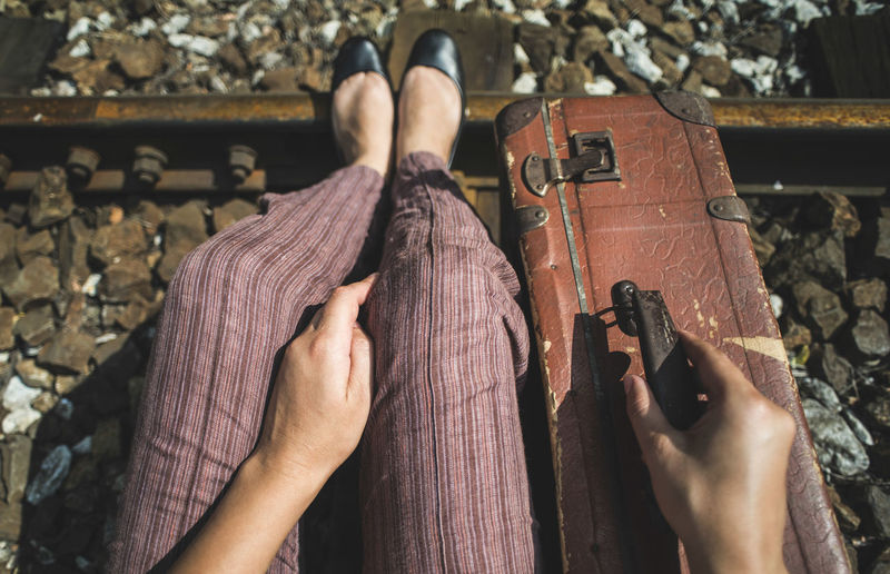 Low section of woman with suitcase sitting on railroad track