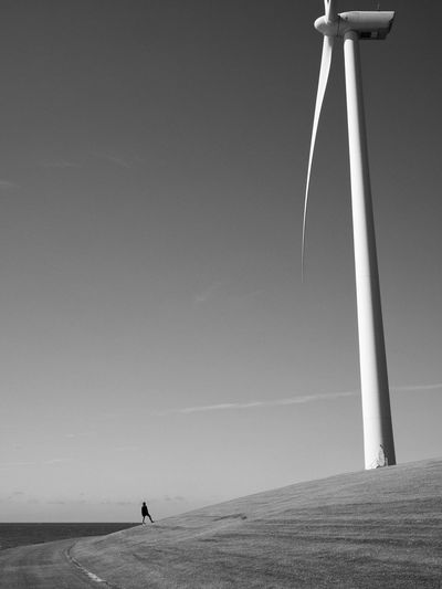 Low angle view of wind turbine on field against sky