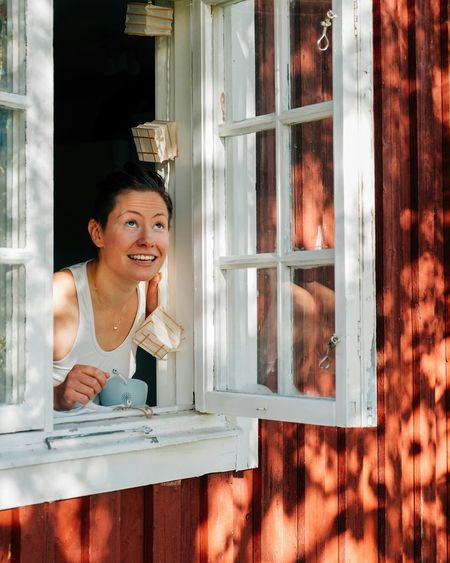 Smiling Mid Adult Woman Looking Through Window
