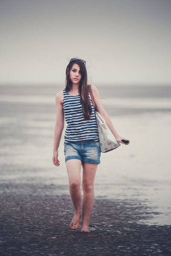 The Portraitist - 2018 EyeEm Awards Beach Beautiful Woman Beauty Casual Clothing Clothing Fashion Front View Full Length Hairstyle Horizon Over Water Land Leisure Activity Looking At Camera One Person Portrait Real People Sea Standing Water Young Adult Young Women