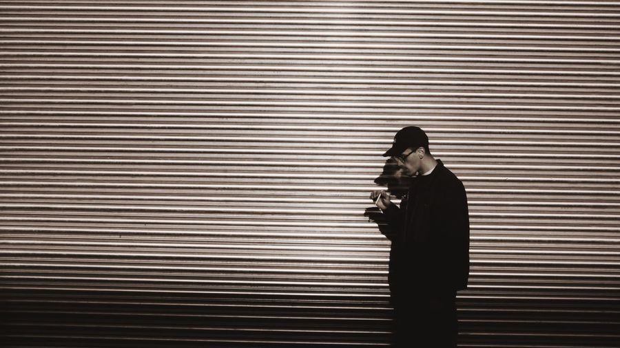 Man smoking while standing against shutter