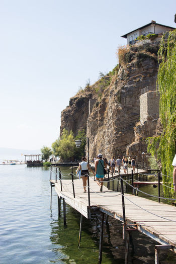 Holiday Starting A Trip Summertime Travel Adventure Architecture Beauty In Nature Building Exterior Built Structure Clear Sky Day Foot Bridge Iaeste Lake Men Mountain Nature Outdoors People Rock - Object Sky Summer Travel Destinations Water Women