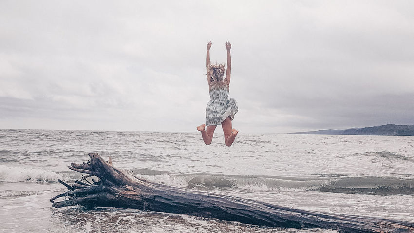 EyeEmNewHere EyeEm Selects Young Women Full Length Beach Jumping Sand Women Sea Sky Horizon Over Water Energetic Spread Wings Arms Raised Energy Agility Acrobat Legs Apart Flexibility Acrobatic Activity Summer In The City