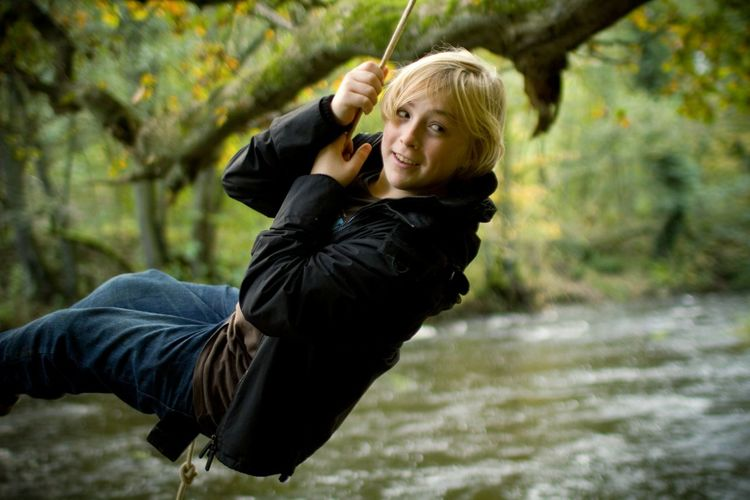 Young woman swinging on rope over river in forest