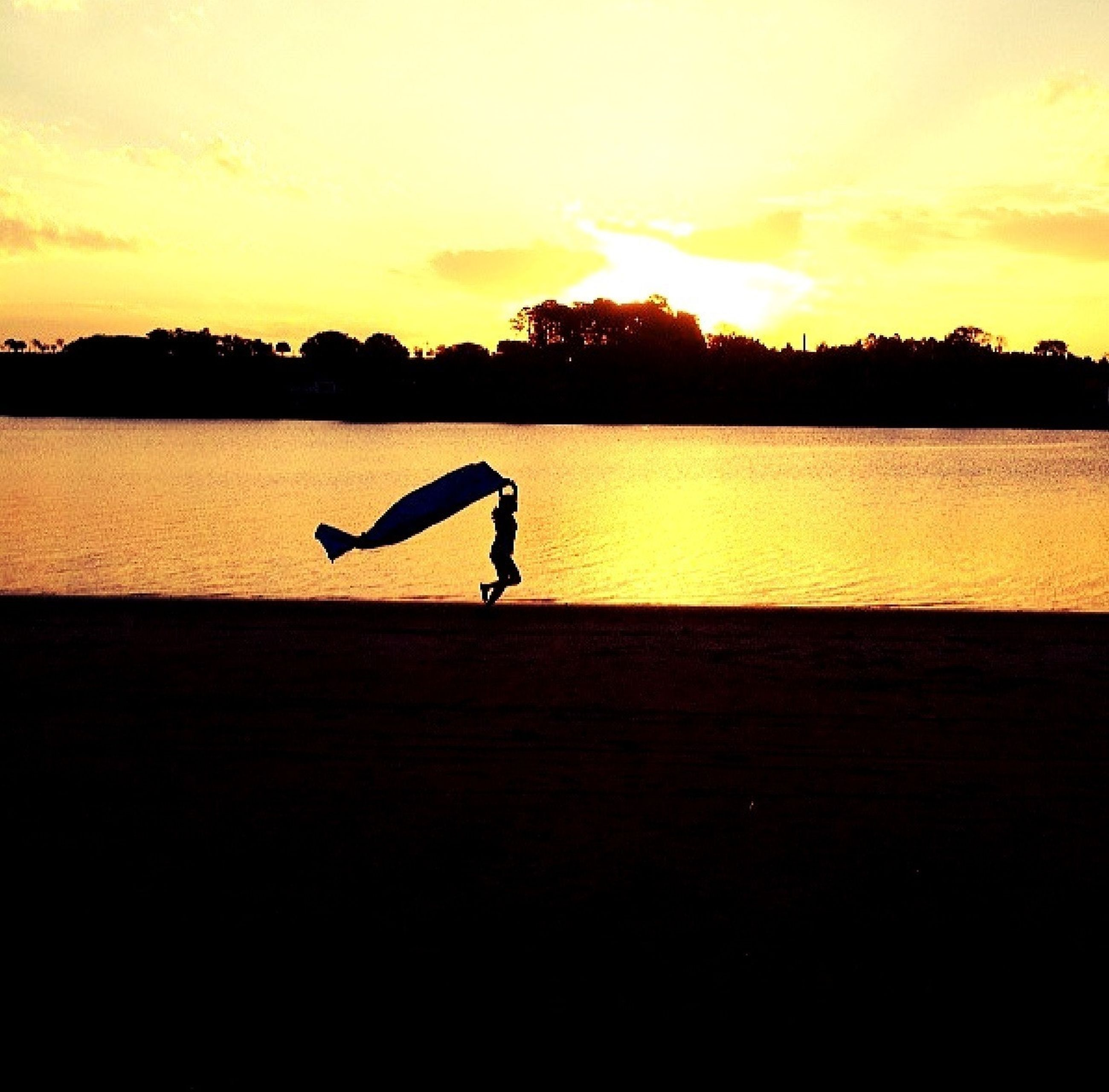 sunset, silhouette, water, orange color, leisure activity, lifestyles, sky, men, beauty in nature, scenics, lake, full length, tranquil scene, tranquility, nature, standing, unrecognizable person, reflection