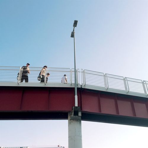Low angle view of people on bridge against clear sky
