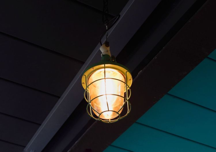 Lantern with orange light bulb hangs from ceiling, blue and black background Ceiling Ceiling Hanging Lantern Orange Light Light Bulb Low Angle View Hanging Lighting Equipment Ceiling Illuminated Electricity  No People Indoors  Built Structure Architecture Night Close-up