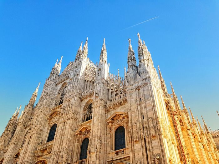Low Angle View Of Milan Cathedral Against Blue Sky