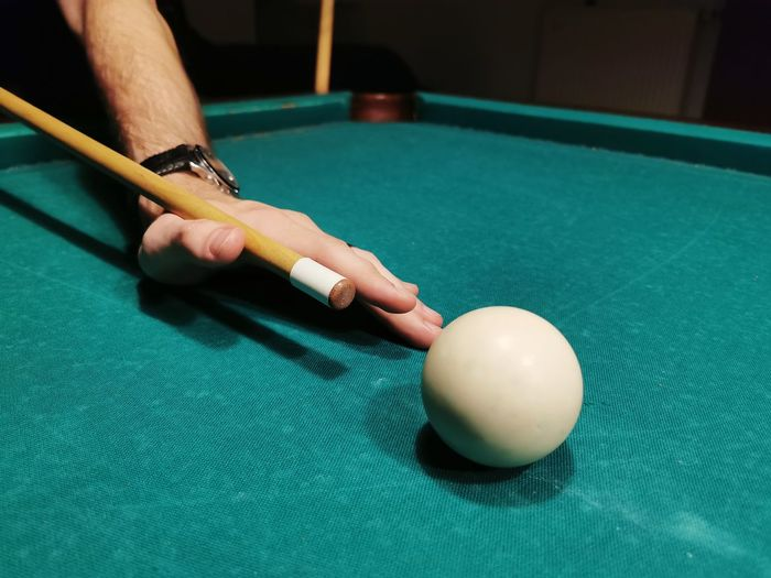 Person playing with ball on table, snooker game