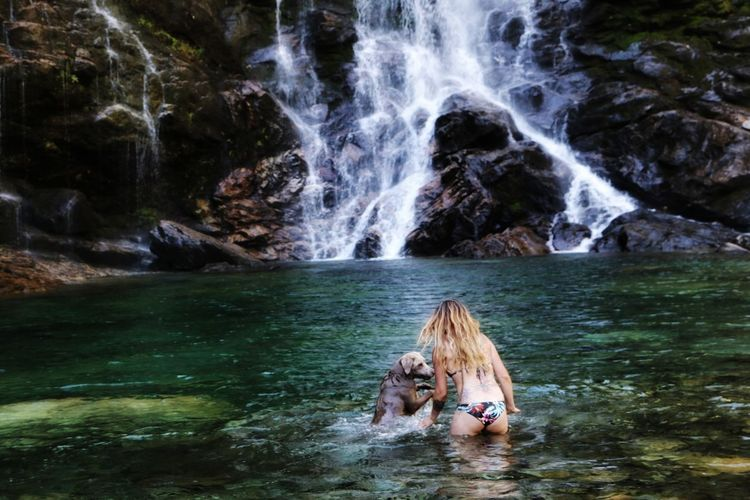 Rear view of woman playing with dog in lake against waterfall