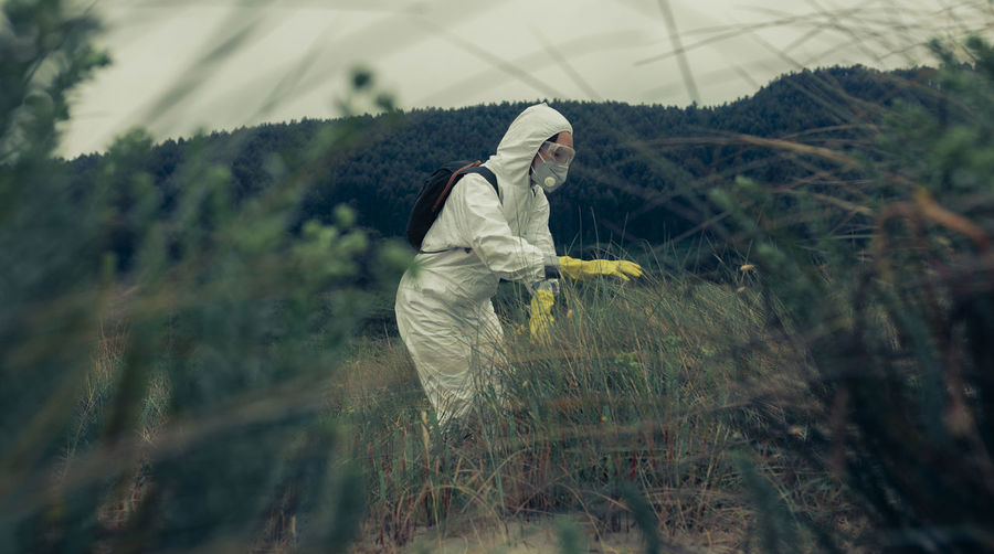 Side view of woman in protective workwear standing by plants