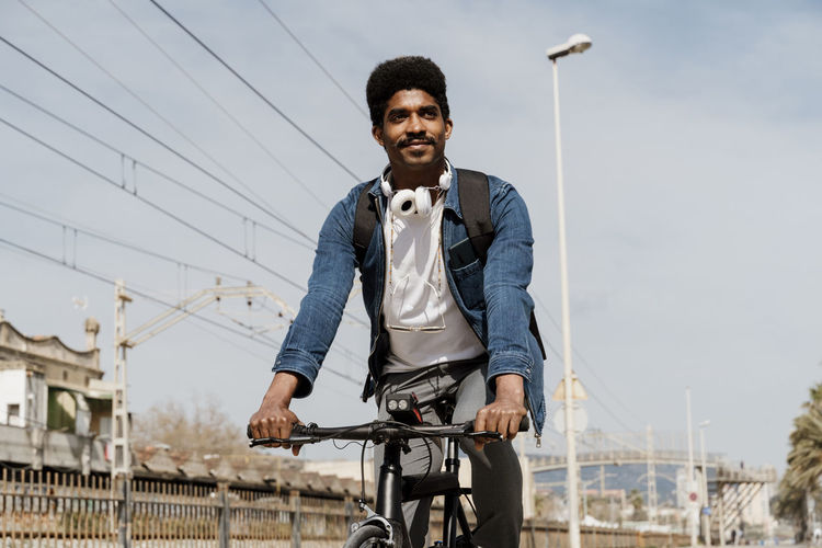 Portrait of young man riding bicycle against sky