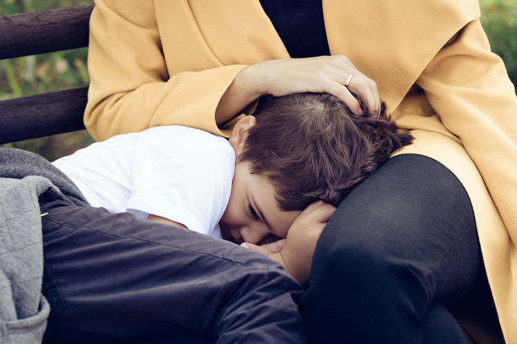 Midsection of mother with son resting on bench