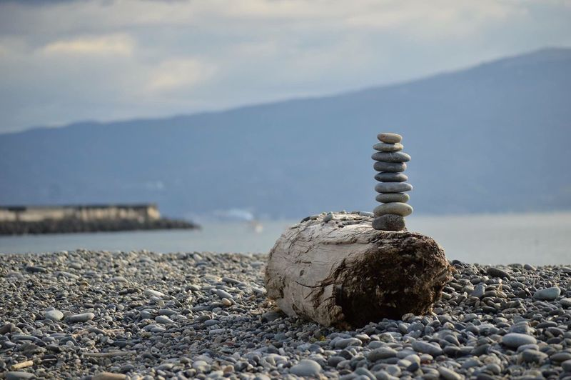 Pebbles Stacked On Driftwood At Sea Shore