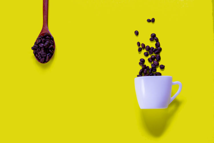 Close-up of coffee cup against yellow background