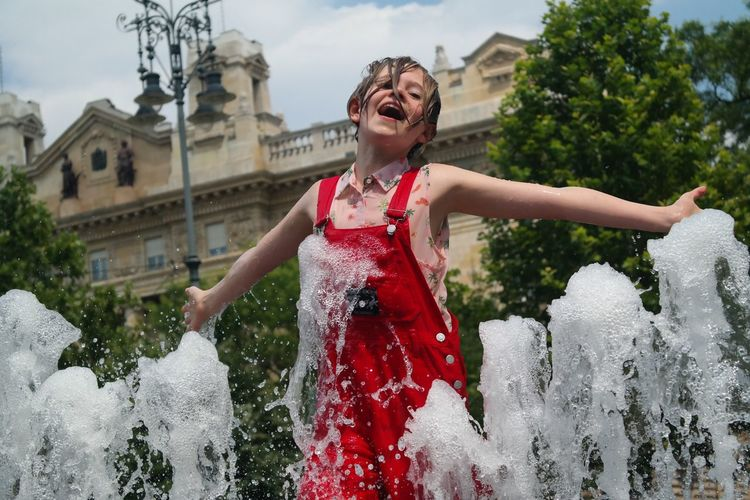 Low Angle View Of Cheerful Girl With Arms Outstretched Amidst Fountain