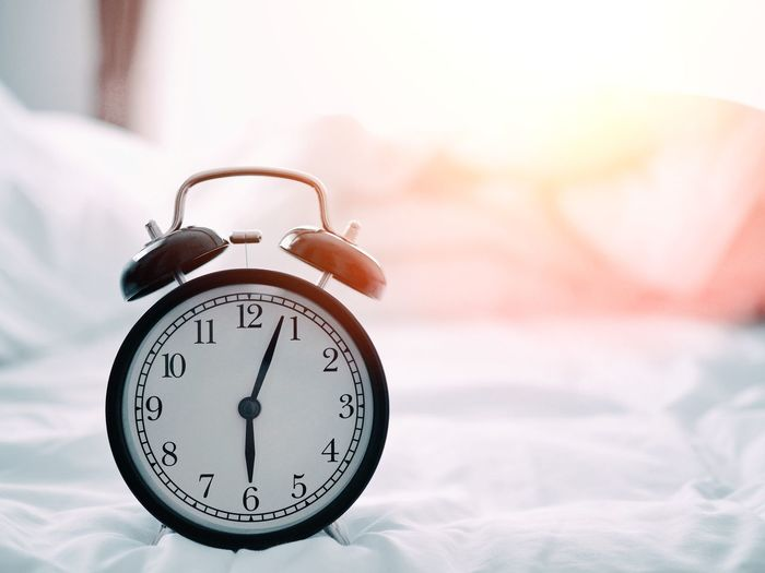 Close-up of alarm clock on bed at home