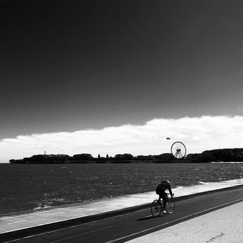 Man riding bicycle on road against sky