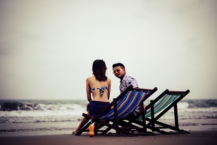 Sitting Sea Two People Beach Water Togetherness Land Couple - Relationship Sky Men Full Length Leisure Activity Nature Young Men People Love Adult Emotion Real People Women Positive Emotion Horizon Over Water Outdoors Care