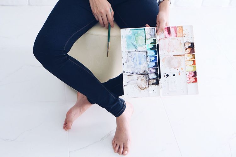 Low Section Of Woman Holding Color Palette On Floor
