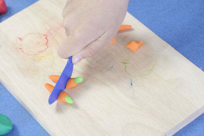 My son plays the clay Children Learning Molding Clay Child Childhood Clay Art Close Up Cutting Board Day Hand High Angle View In Door In Home Making Playing Real People