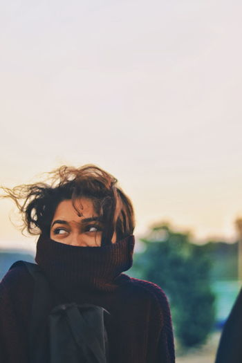 Woman in warm clothing looking away during sunset