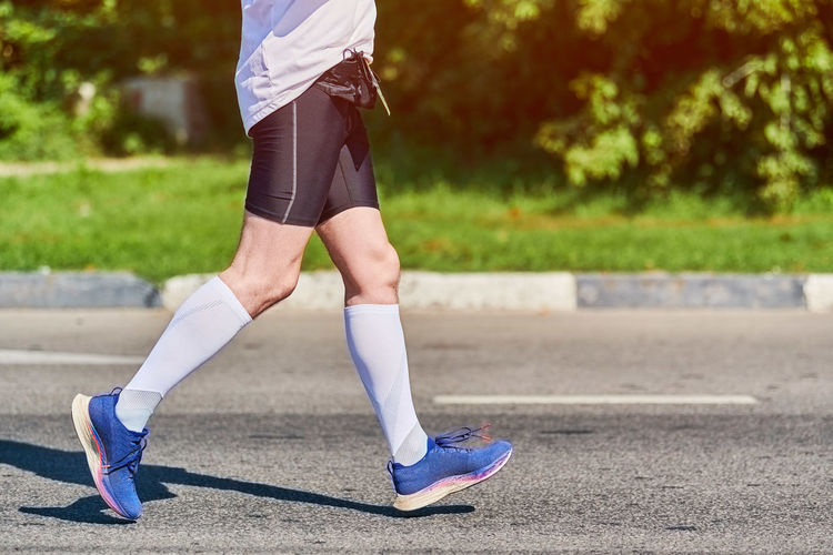 Low section of man running on road
