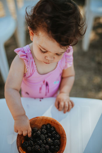Baby girl picking blackberry from bowl