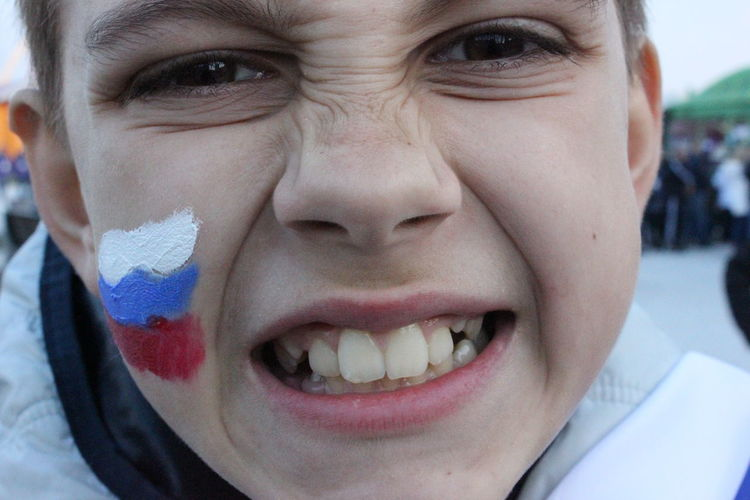 Close-up portrait of teenage boy making face