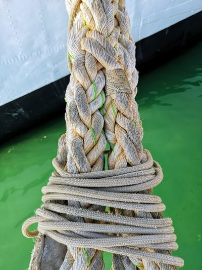 Stack of rope tied to wooden post in lake