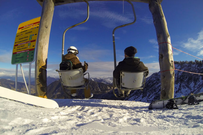 Couple enjoying stunning view from the top of a mountain in funny chairlift swing Chairlift View Mountain View Swinging Chairlift Cold Temperature Couple - Relationship Day Friendship Mountains Outdoors Real People Sitting Ski Holiday Snow Snowboarding Swing Winter Shades Of Winter Go Higher