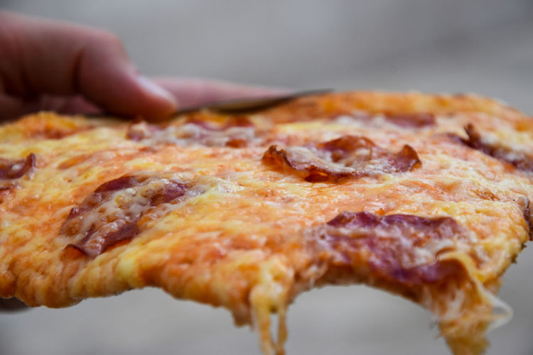 Cropped hand having pizza