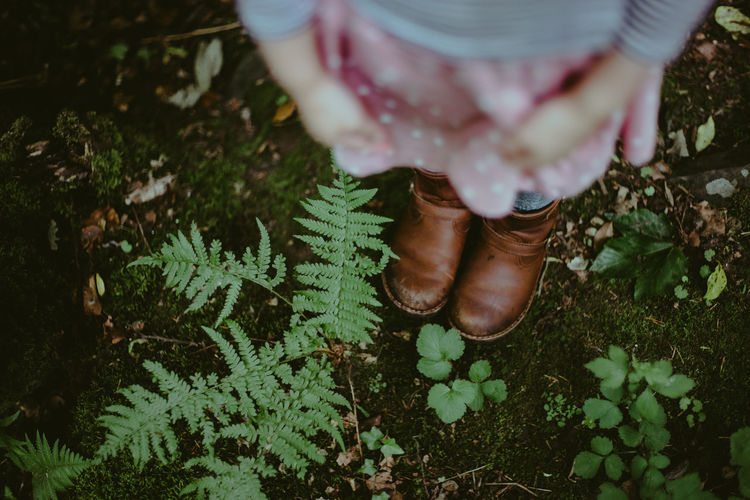 Low section of girls boots standing on ground near plants