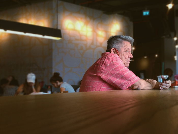 Side view of senior man looking away while sitting at table in restaurant
