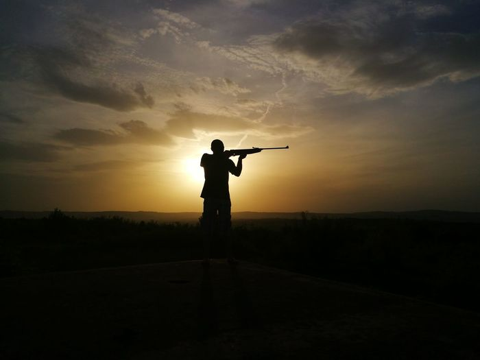 Silhouette Man Shooting Rifle On Field Against Sky During Sunset