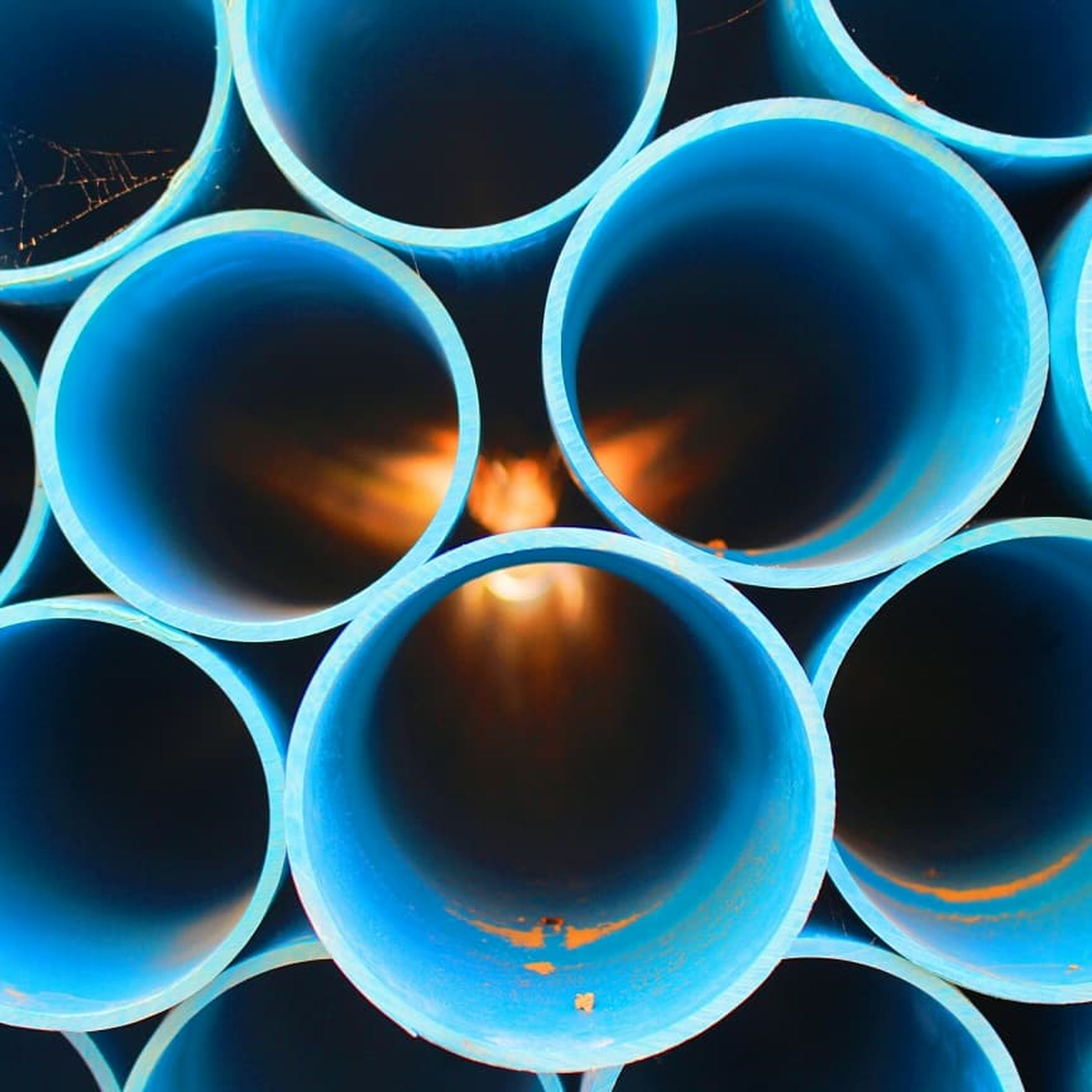 circle, geometric shape, shape, close-up, no people, pipe - tube, backgrounds, design, full frame, stack, pattern, abstract, large group of objects, blue, industry, group of objects, fuel and power generation, day, indoors, blue background